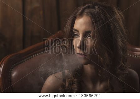 Woman with professional makeup in black lingerie smoking