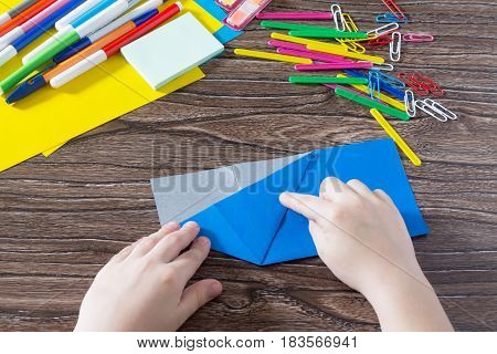 The Child Folds The Paper Parts. Different Paper And Office Accessories On A Wooden Table. The Proje