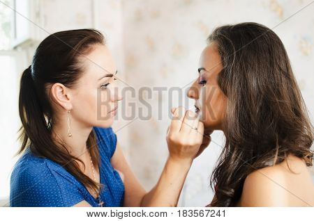 Lady closes her eyes while the artist paints her lips
