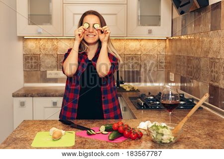 Happy woman having fun with cucumber at kitchen. Woman cooking dinner vegetable salad.