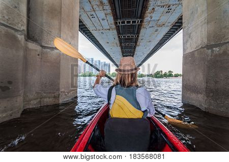 Meeting morning on kayaks. Rear view of young girl kayaking bu the river and under the bridge. Urban exploration concept.