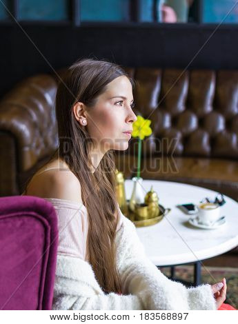 Beautiful girl dreaming about something while sitting in a cafe and looking at window. Young charming woman thinking about new ideas, drink a coffee, sitting on a lilac armchair in a modern city bar.