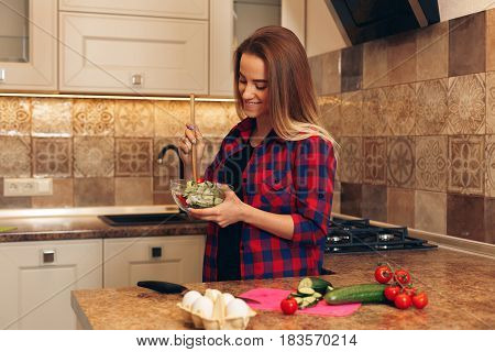 Starting day with healthy food. Beautiful young mixed race woman eating salad and looking away while standing in kitchen at home.