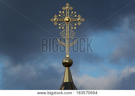 Yoshkar-Ola, Russia - April 25, 2017 Photo of an Orthodox Christian cross on a background of gloomy clouds