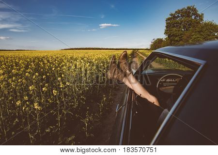 Summer fun vintage car. Legs showing from muscle car. Freedom, travel and vacation road trip concept lifestyle image