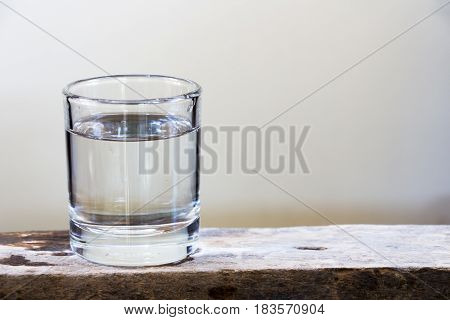Drinking water in glass on a wooden floor.