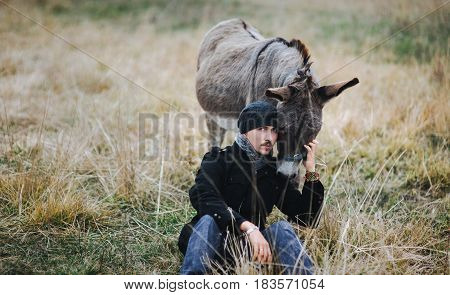 The young guy sits near the donkey. Friendship between man and animals in greenpeace.