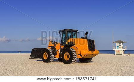 Mechanical shovel performing cleaning on Clearwater Beach, Tampa, Florida