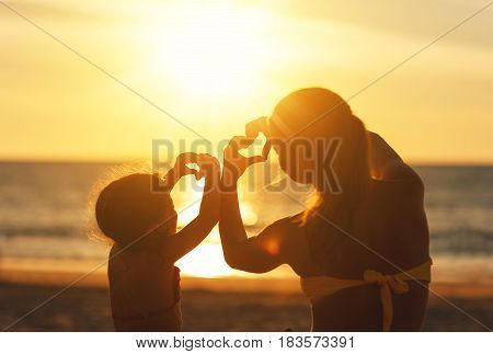 The concept of love parenthood and a happy family. Mother and child daughter show heart from hands at sunset on beach