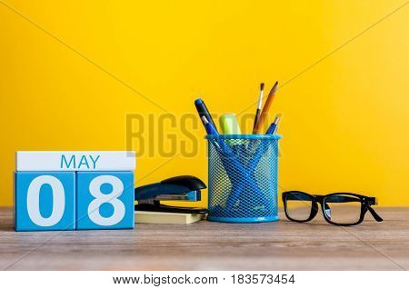 May 8th. Day 8 of month, calendar on business office table, workplace at yellow background. Spring time.
