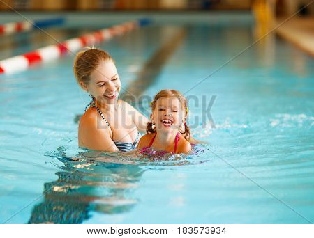 Mother teaches child daughter to swim in pool