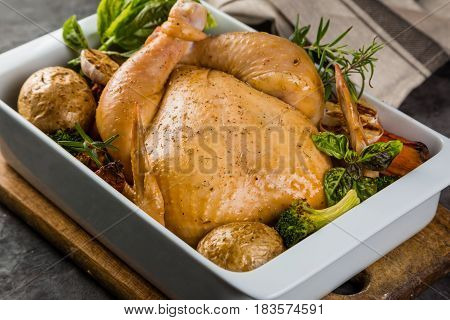 Roasted whole chicken with herbs and spices on rustic background