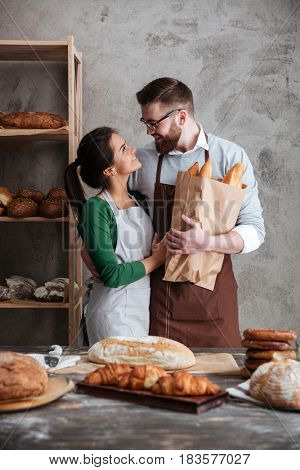 Vertical image of a happy bakers which hugging and looking to each other in bakery while man holding bag with bread