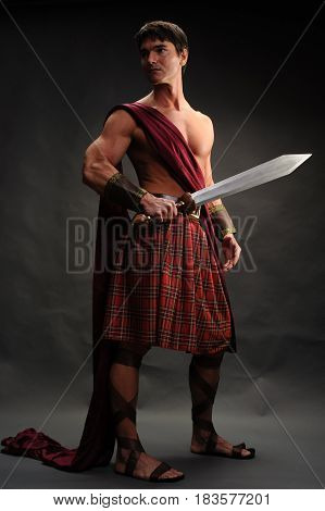 The tough highlander is showing off his sword.