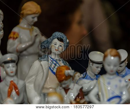 Moscow, Russia - March 19, 2017: Old antique porcelain and ceramic figures for sale on the flea market. Toy and collectibles. Selective focus