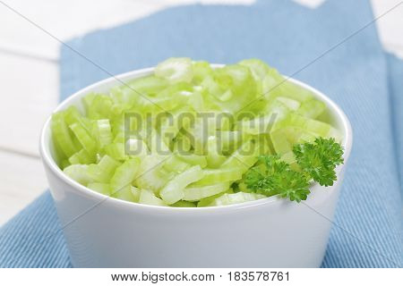bowl of chopped celery stems on blue place mat - close up