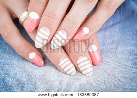 Beautiful female manicure close-up, on blue jeans