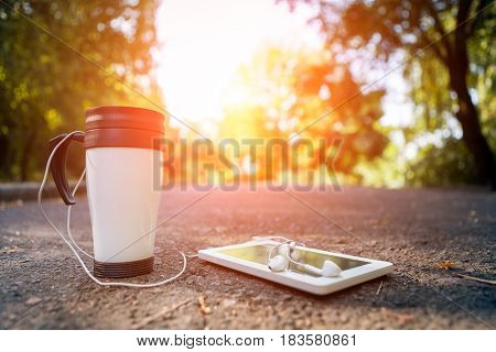 cup of tea, a white plane-table with headsets lies on the road