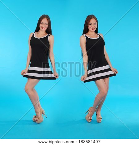 Cheerful young girl are standing against the blue background. Mirror reflection.