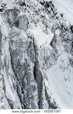 Snow Covered Cliffs And Glacier Crevasses In Winter