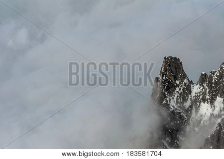 Single Mountain Peak Emerging From Thick Cloud Cover
