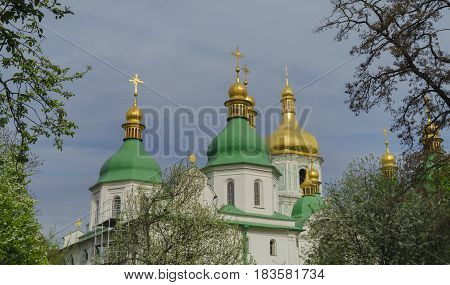 Orthodox church with green domes and golden crosses against the blue sky in the spring