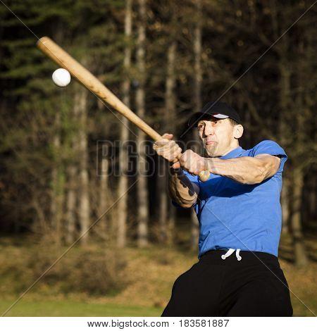 The man is playing baseball shooting the ball.