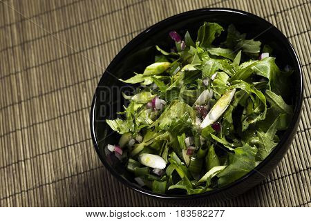 Vegan salad meal with green salad and spring onion.