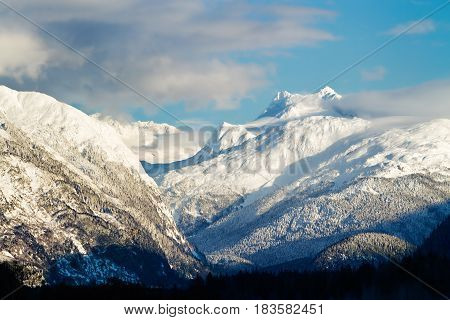 Pristine snow capped mountains surrounded by clouds