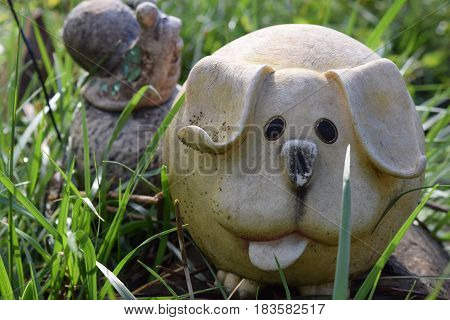 Garden decor of a fat dog and a big snail in the background during Spring.