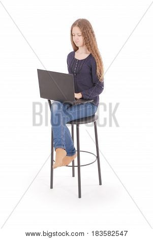 Girl sits on a chair and holding a laptop computer isolated on white