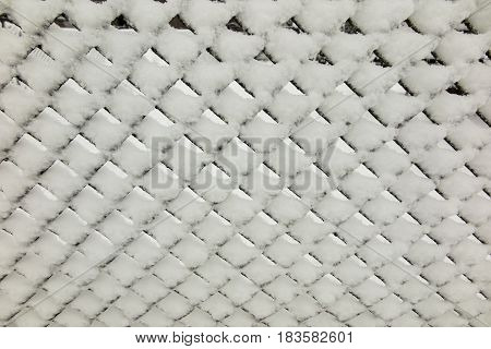 Fresh snow on metal mesh as background