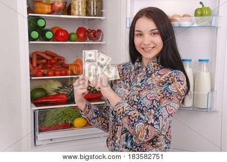 Young girl holding dollars on the refrigerator background. Beautiful young girl near the fridge.