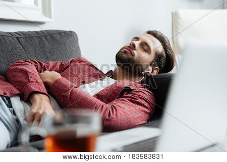Picture of handsome young man lies on sofa indoors at home while listening music with earphones. Eyes closed.