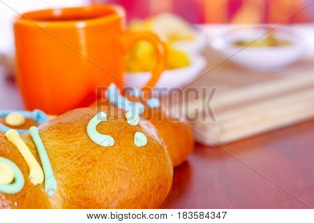 Elegant setup traditional tasty latin american guagua breads, colorful sugar decorations, orange cup with colada morada berry juice next to it, day of the dead concept.
