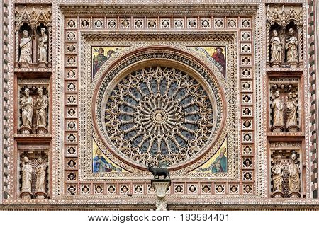 The Orvieto Cathedral central rose window. This cathedral is a 14th-century Roman Catholic cathedral dedicated to the Assumption of the Virgin Mary and situated in the town of Orvieto in Umbria, Italy