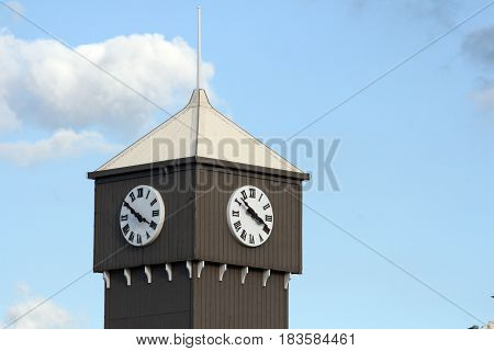 The clock face showing time on a clock tower sky and clouds in the background