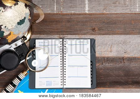 Notebook, Globe And Air Ticket On Wood Background