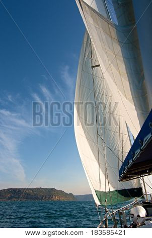 Coastal cruising sailing yacht under full sail at sea heading to Broken Bay with a vivid blue sky backdrop. New South Wales Australia.
