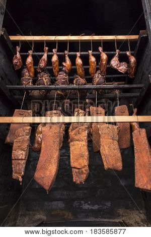 Ready-smoked meat in the smokehouse. Stages of smoking. Raw meat in a smokehouse. Meat prepared for smoking