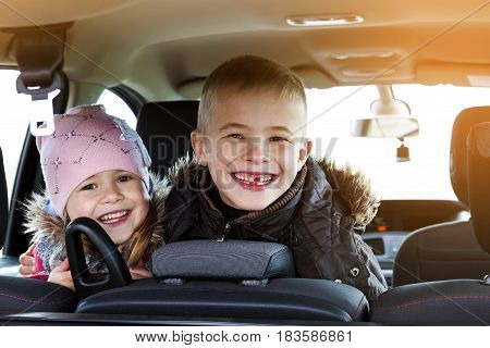Two pretty little children boy and girl in a car interior travel concept. Soft light effect