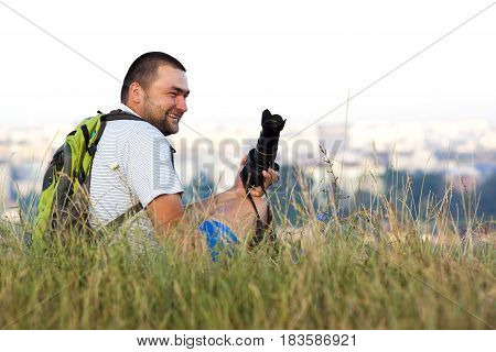 Happy smiling photographer sitting in grass in summer with a camera