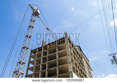 Modern Building Under Construction Against Blue Sky. Tower Crane Construction Work Site