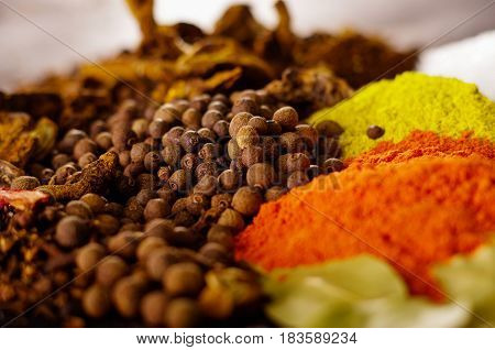 Closeup from above different piles of colorful spices, beautiful rustic setting, spice and herbal concept.
