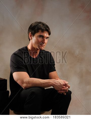 The sexy man is seated looking very muscular.