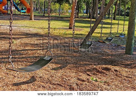 Public child's swing-set at a playground at a park. There are also other gaming devices trees and blue sky in the background