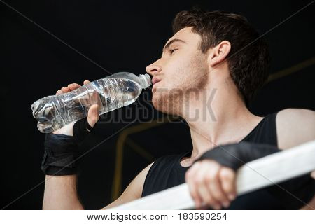 Low view of boxer drinking water with enjoyment on ring