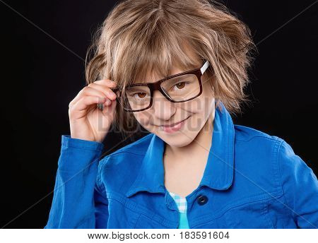 Emotional portrait of attractive caucasian little student girl with eyeglasses. Funny cute smiling child looking at camera on black background.