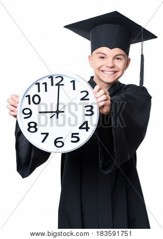 Portrait of a graduate teen boy student in a black graduation gown with hat, holding big clock - isolated on white background. Child back to school, educational and time concept.