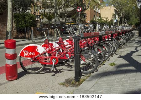 Barcelona Spain - 26 March 2017: Row of parked bicycles for rent. These red bicycles are very popular among citizens of Barcelona.